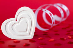 White heart with ribbon and red hearts on red Royalty Free Stock Photo