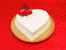 White heart shape cake. White heart cake with red marzipan roses on red background Stock Photo