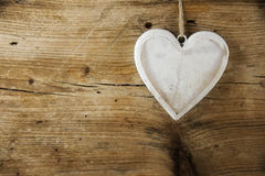 White heart shape made from wood hanging on a rustic wooden wall Royalty Free Stock Photos