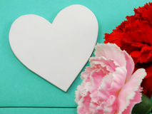 White heart shape symbol and artificial carnation flower valentines day Stock Photos