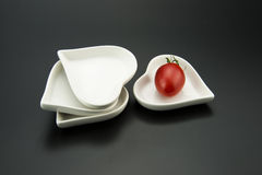 White heart-shaped dish, and small red tomatoes Royalty Free Stock Image