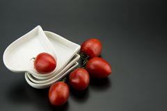 White heart-shaped dish and small tomatoes Stock Photos
