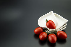 White heart-shaped dish and small tomatoes Royalty Free Stock Photography