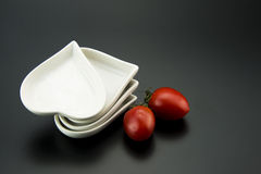 White heart-shaped dish and small tomatoes Stock Photography