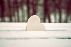 White heart on snow-covered park bench stock photo