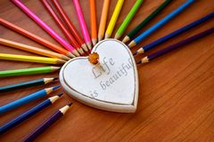 White heart surrounded by colored pencils Stock Photography