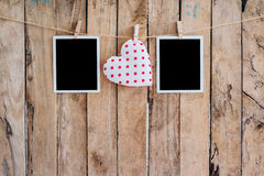 White heart and two photo frame hanging on clothesline rope with Stock Image