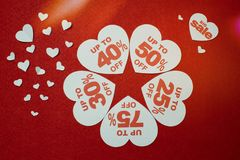 White hearts shaped sales promotion tag against a red background stock images