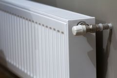 White heating radiator with thermostat valve on wall in an apartment interior after renovation works. White heating radiator with thermostat valve on wall in an Royalty Free Stock Photo