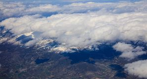 White heavy clouds background hanging on blue sky over mountain. Aerial photo from plane`s window. White heavy clouds background hanging on blue sky over Stock Photo