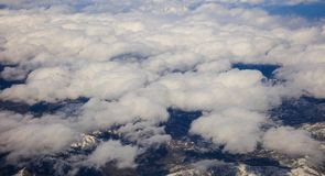 White heavy clouds background hanging on blue sky over mountain. Aerial photo from plane`s window. White heavy clouds background hanging on blue sky over Stock Photography