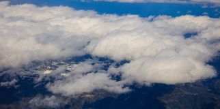 White heavy clouds background hanging on blue sky over mountain. Aerial photo from plane`s window. White heavy clouds background hanging on blue sky over Royalty Free Stock Images