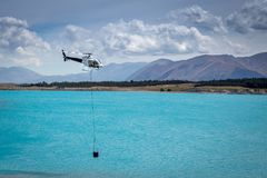 A white helicopter returns to the lake to refill its monsoon bucket to fight a fire stock photo