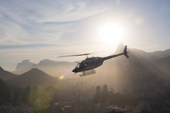 White Helicopter Under Gray Buildings Near Mountains Royalty Free Stock Photography