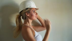 White helmet and blue metal ladder in aparment construction site. Young woman builder in white top and jeans shorts stock footage