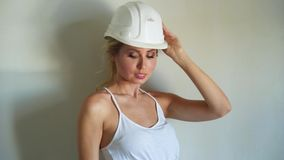 White helmet and blue metal ladder in aparment construction site. Young woman builder in white top and jeans shorts stock video