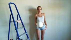 White helmet and blue metal ladder in aparment construction site. Young woman builder in white top and jeans shorts stock video footage