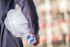 White helmet and blueprints on construction site Stock Image