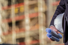 White helmet and blueprints on construction site Royalty Free Stock Image