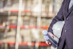 White helmet and blueprints on construction site Stock Photography