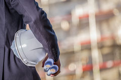 White helmet and blueprints on construction site Royalty Free Stock Photo