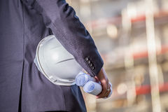 White helmet and blueprints on construction site Stock Images