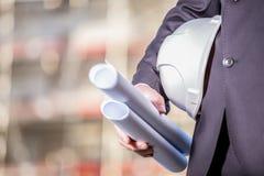 White helmet and blueprints on construction site Stock Photos