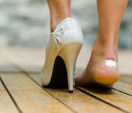 White high heel in one feet and other injured with white little patch. Feet on toe Royalty Free Stock Photo