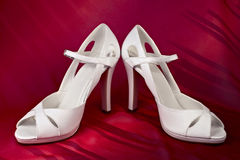 White high-heeled shoes. Over red background Stock Image