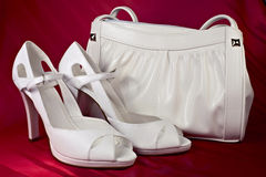 White high-heeled shoes and handbag. Over red background Royalty Free Stock Photo