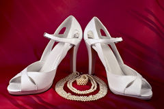 White high-heeled shoes and pearls Stock Images