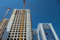White high-rise building under construction and tower cranes against the blue sky royalty free stock photos