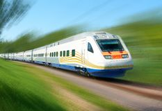 White high speed railway train runs on rail tracks among green trees. Train in motion. Motion blur. Effect Stock Photo