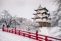 Hirosaki Castle and its red wooden bridge in winter season, Aomo. White Hirosaki Castle and its red wooden bridge in mid winter season, Aomori, Tohoku, Japan Royalty Free Stock Photography