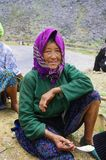White Hmong grandmother in lunch. This woman is wrinkled by the hard work the fields. The region is mountainous Ha Giang and arid. The land is rare among the Stock Photos