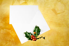 White holiday card & envelope. White card and envelope with holly  over a gold hand painted background Stock Photos