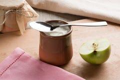 White homemade yogurt in a clay jar with an apple stock photos