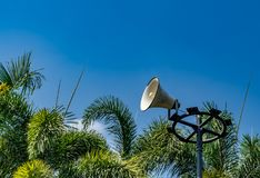 White horn speaker. On blue sky and palm tree leaves background in the park Royalty Free Stock Photography