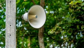 White horn speaker. On concrete pole Stock Photo