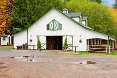 White horse barn wuth green shatters. Royalty Free Stock Image