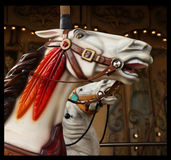 White horse in Carousel. White horse with brown hair and red feathers in a carousel at the fair Stock Photos