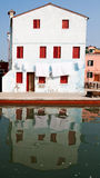 White house. White house reflecting in a canal on the island Burano, Italy stock image