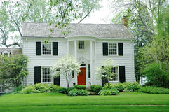 White House. White fromal house with siding, black shutters and bright green, manicured lawn / garden royalty free stock photos