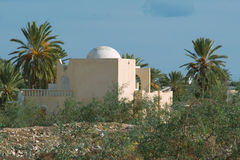 White house in arabic style on Djerba. Surrounded by beautiful green trees, white house in arabic style on Djerba, Tunisia Stock Photo