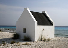 White house on the beach. Small white slave house on a sandy caribbean beach in Bonaire Royalty Free Stock Photo
