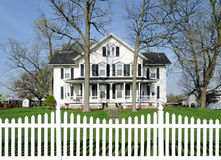 White house with black shutters. And white picket fence Royalty Free Stock Image
