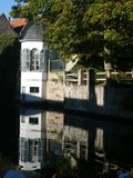 A white house and a brick wall reflected in a canal. A white house with grey shutters stands beside a brick wall. Both are reflected in the ripples of a canal Stock Images