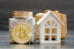 White house, coin Bitcoin and gifts on black background.  Royalty Free Stock Image