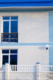 White House with French Balcony. Front of a white house with a blue metal roof and a second story french balcony.  In the photo are two patio doors and a white Royalty Free Stock Photo
