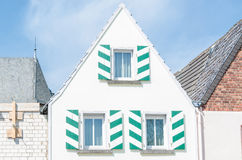 White House Gable. White House front gable with shutters in white green. Blue sky with clouds Royalty Free Stock Photo